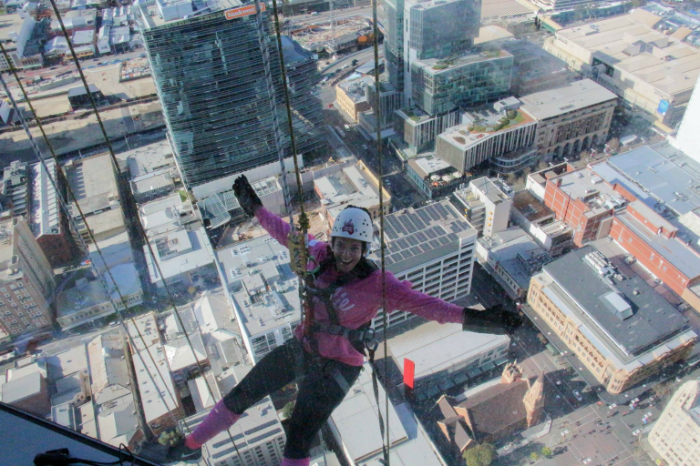 Woman abseiling with view of of city buildings in background
